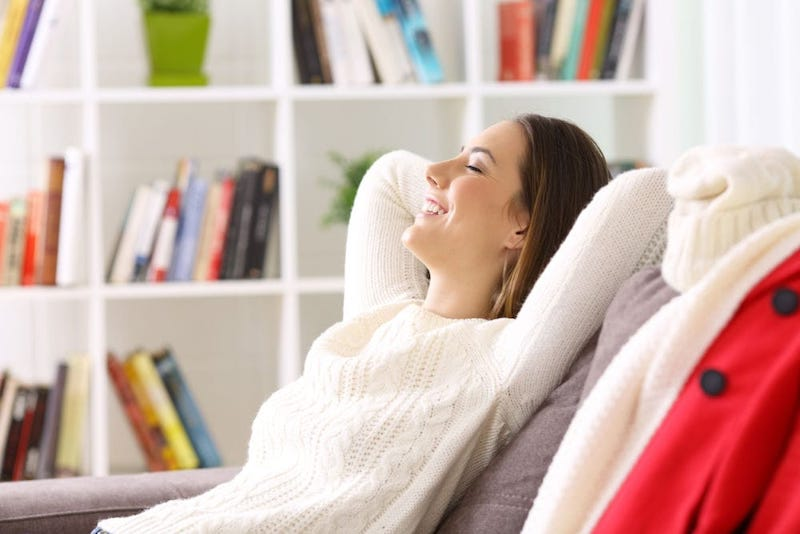 Woman relaxing on the couch in her home that has great indoor air quality.