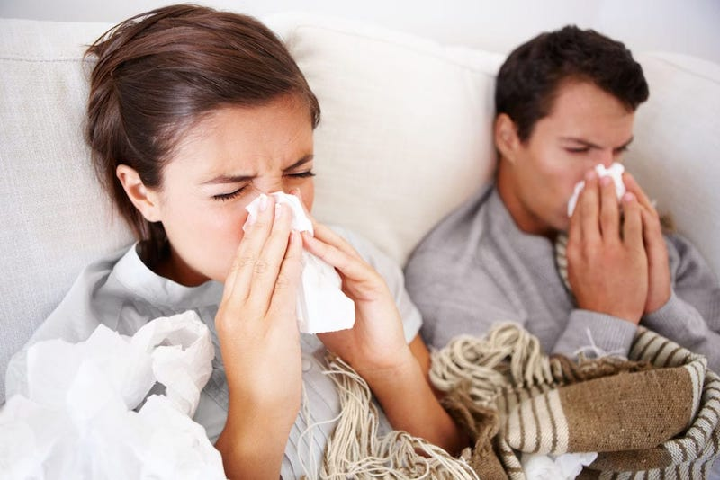 Two people sick in bed blowing their nose.