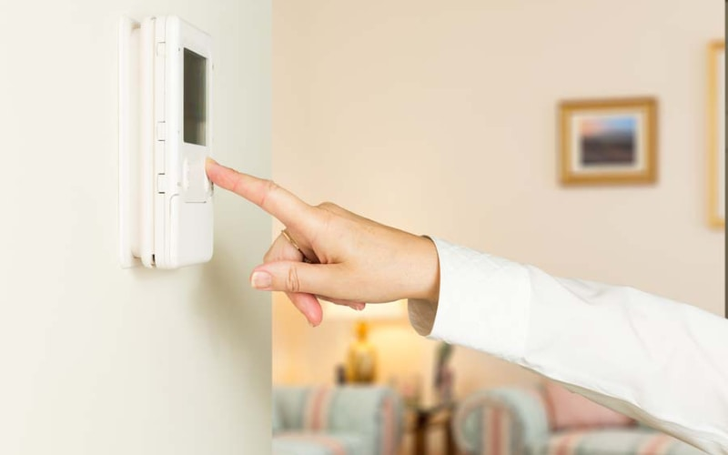 Woman changing the thermostat in her Laguna Hills, CA home.