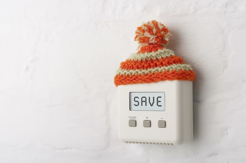 SAVE written on a digital thermometer with a winter hat on it.