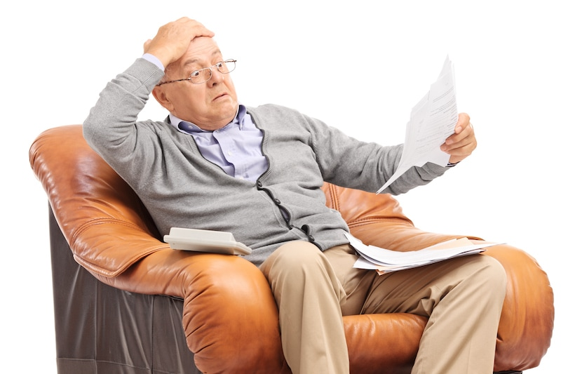 Have Your Utility Bills Jumped?, Shocked senior man looking at his bills in disbelief,