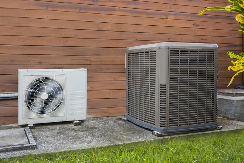 Air conditioning heat pumps on the side of a house in need of a chemical wash